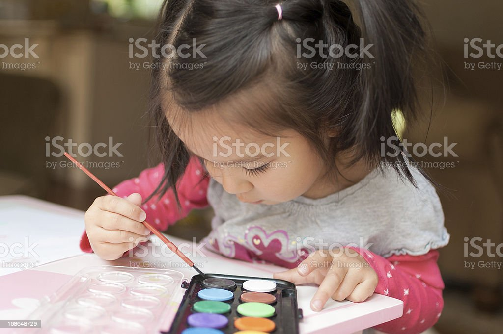 Little Asian girl learning to paint with watercolors at home royalty-free stock photo