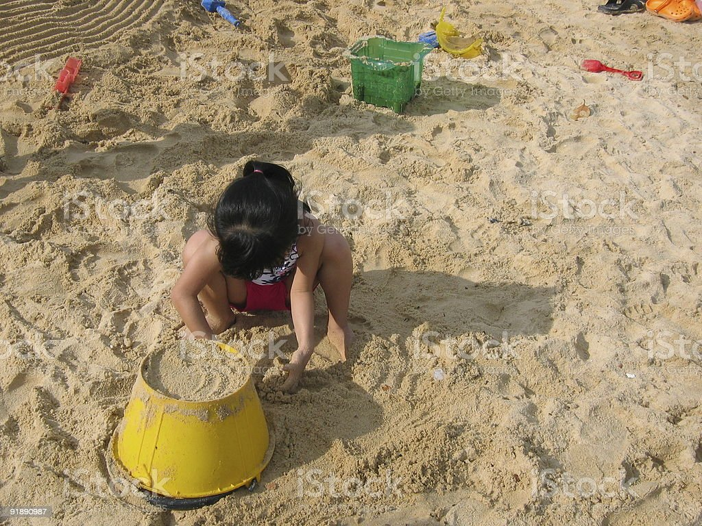 Little asian girl playing with sand stock photo