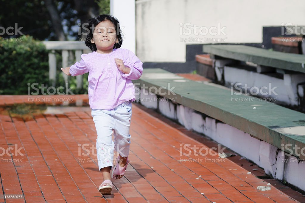 little asian girl running on red pavement royalty-free stock photo