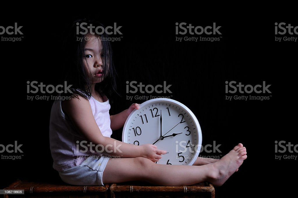 Little Asian Girl Sitting and Holding Clock, On Black Background stock photo