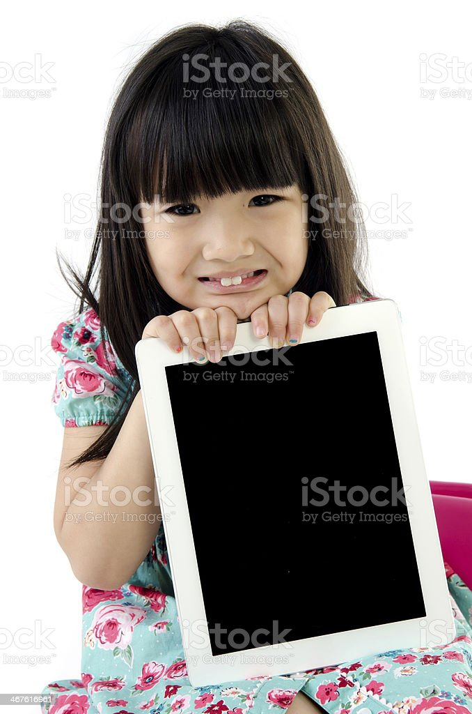 Little asian girl smiles with tablet computer royalty-free stock photo