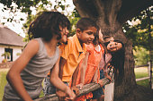 Little asian girl smiling on fence with friends in park