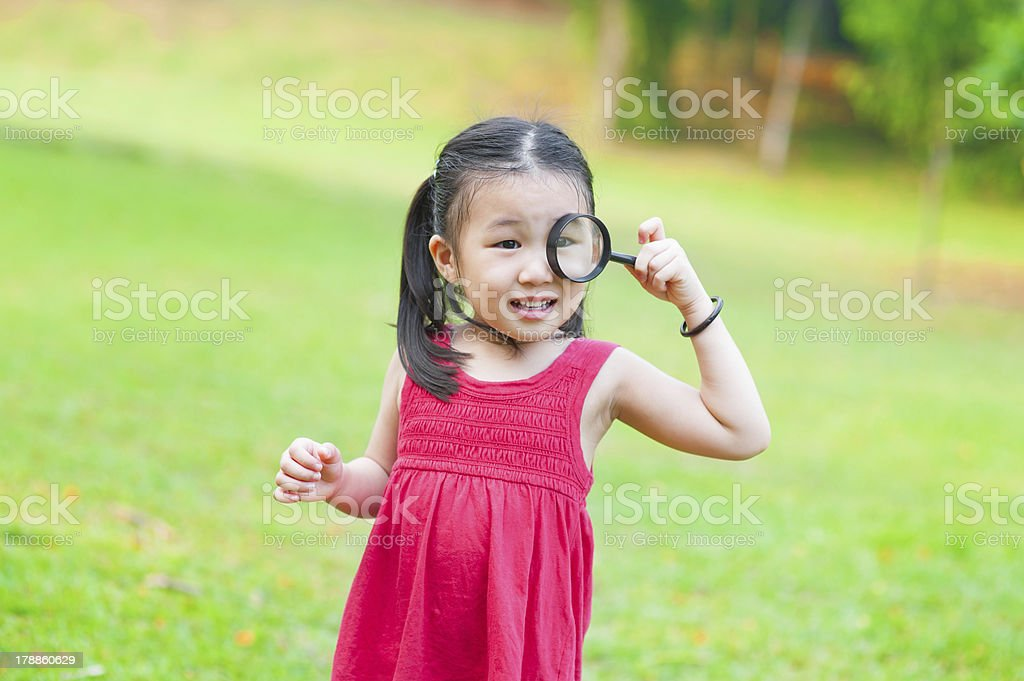 Little Asian girl with magnifier glass royalty-free stock photo