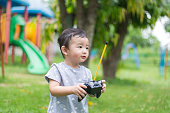 Little Asian kid holding a radio remote control. shallow DOF