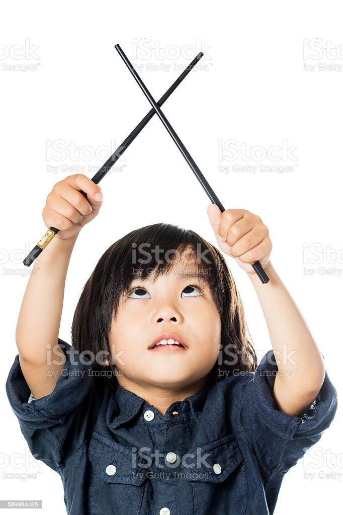 Little Asian kid with chopsticks looking up. photo libre de droits