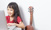 Little Asian musician is taking music class online.