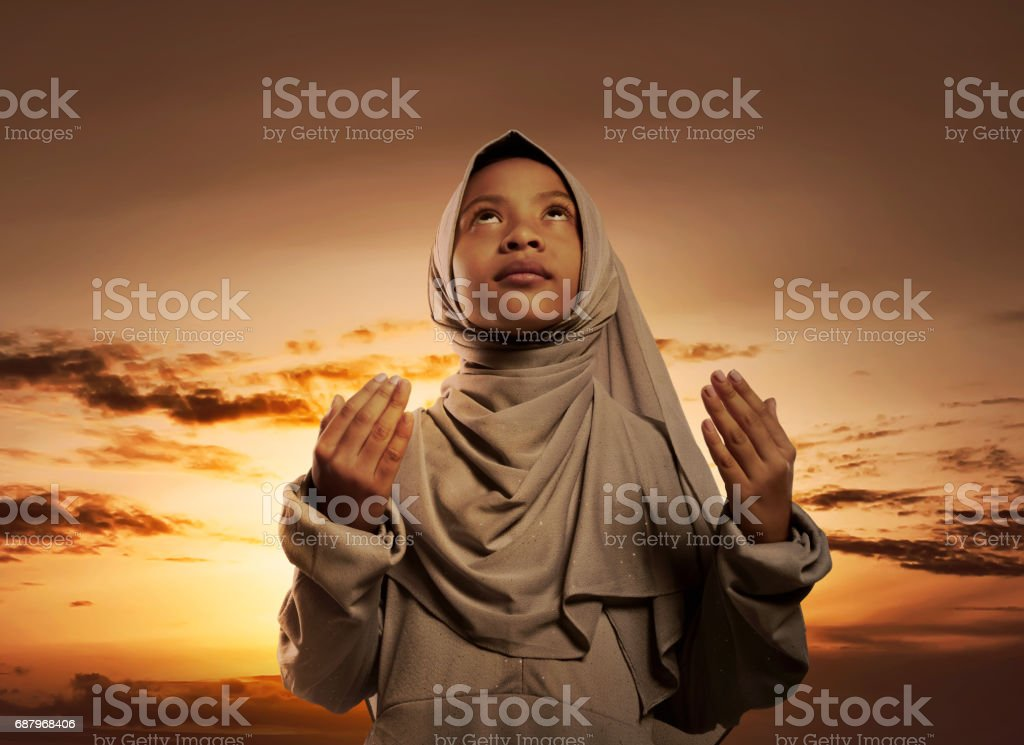 Little asian muslim girl with hijab praying to god stock photo