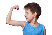 Little athletic boy looking at biceps muscle isolated