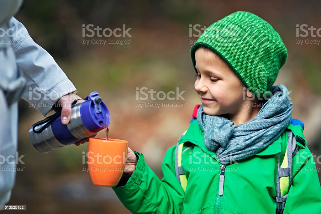 Little autumn hiker drinking hot tea stock photo