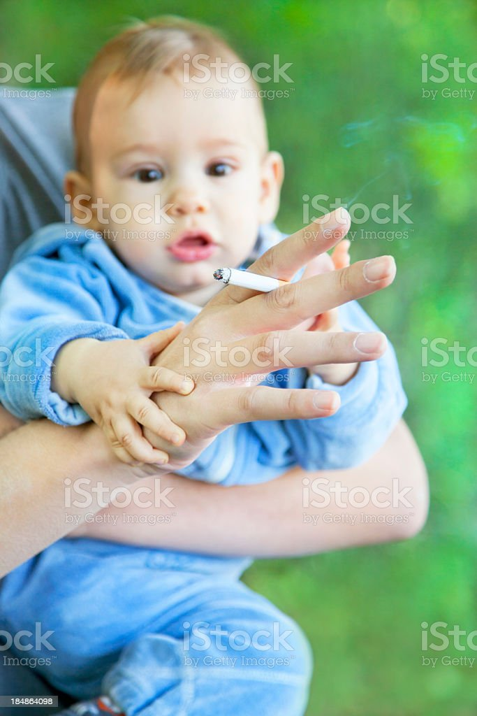 A little baby behind a hand with a lighted cigarette stock photo