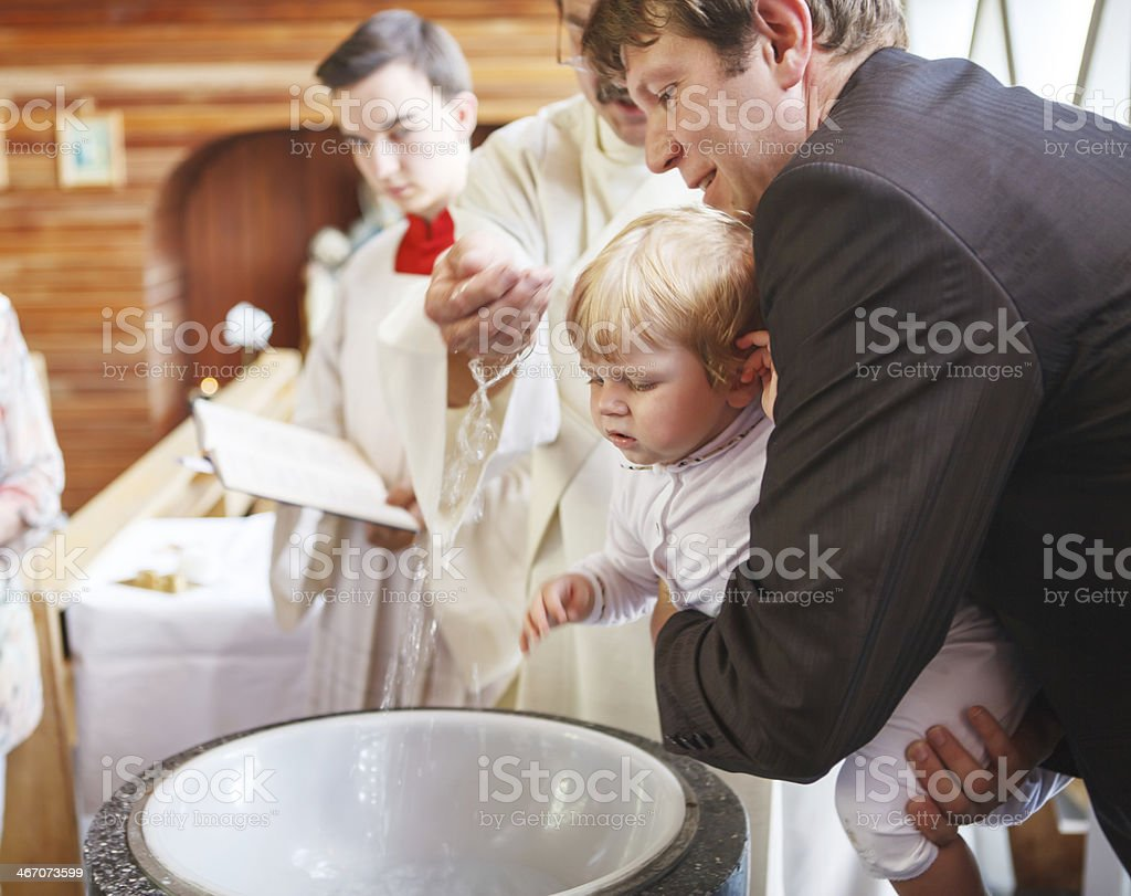 Little baby boy being baptized in catholic church holding stock photo