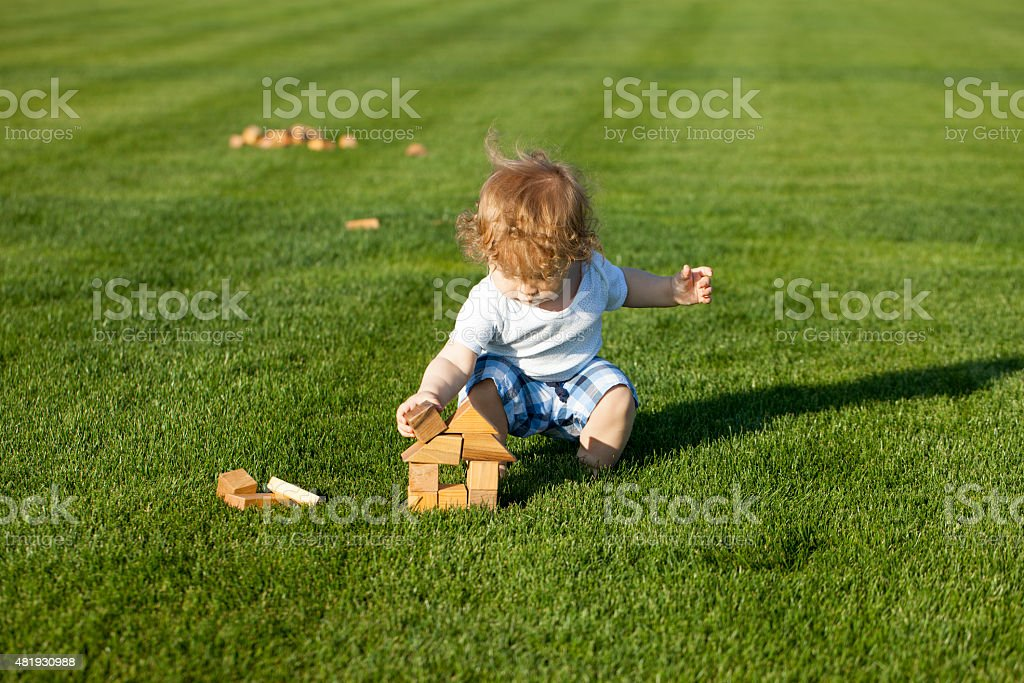 Little baby boy builds a wooden house stock photo