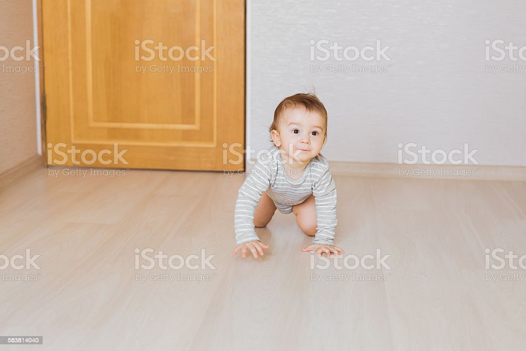 Little baby boy crawling on the floor at home stock photo