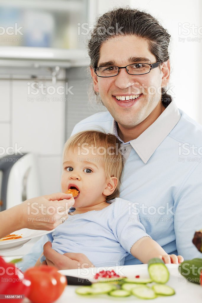Little baby boy eating in the kitchen with parents. royalty-free stock photo