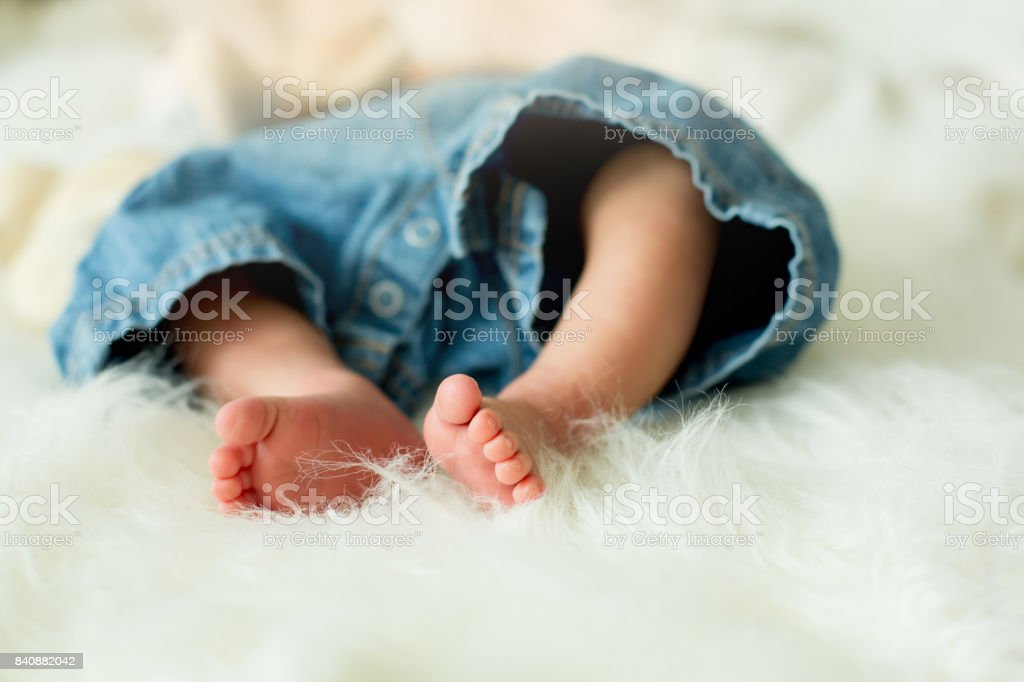 Little baby boy feet, baby lie down in bed in the afternoon stock photo