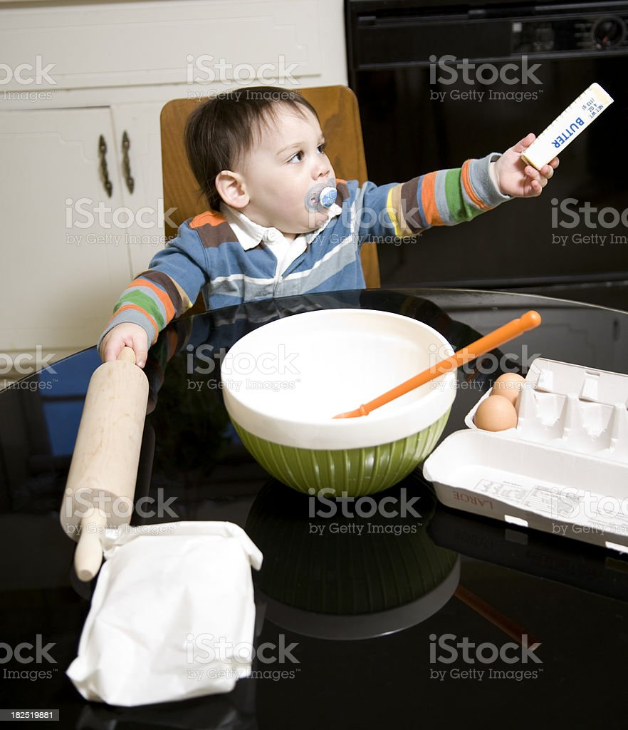 A little baby boy is preparing to bake with a rolling pin royalty-free stock photo