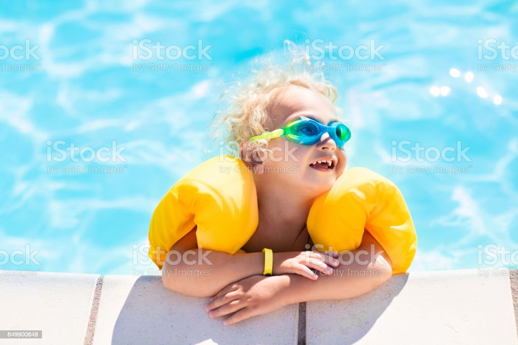 Little baby boy playing in swimming pool royalty-free stock photo