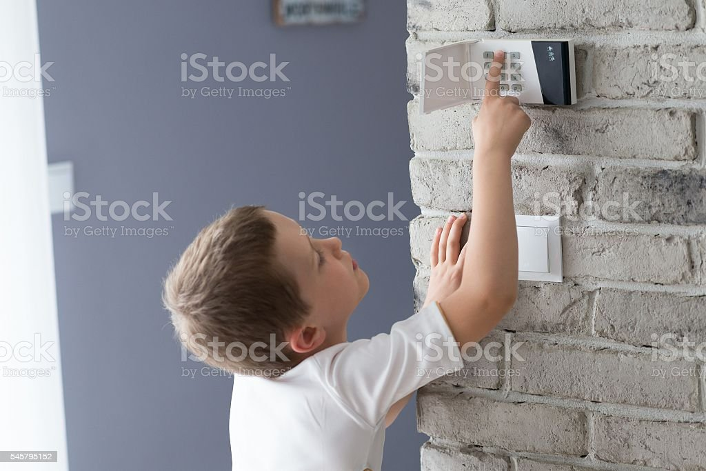 Little baby boy pushes a buttons on the alarm keypad stock photo