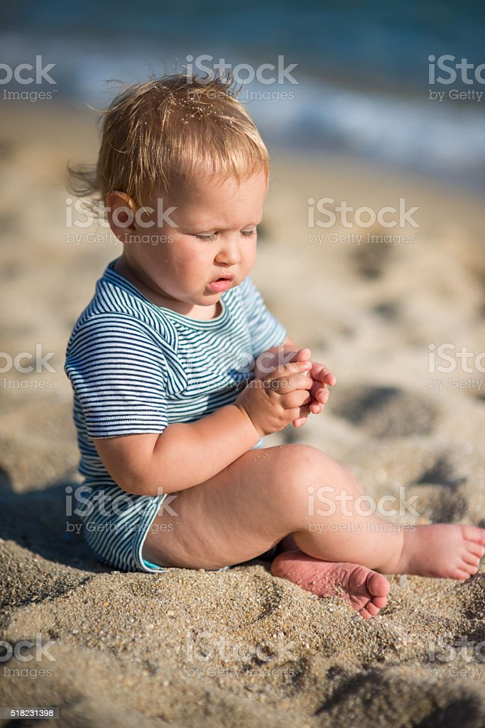 Little baby boy sitting on the sand stock photo