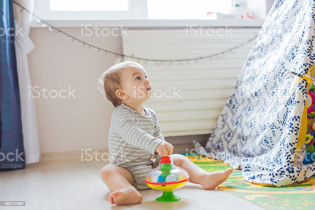 Little baby boy with a toy playing on the floor stock photo