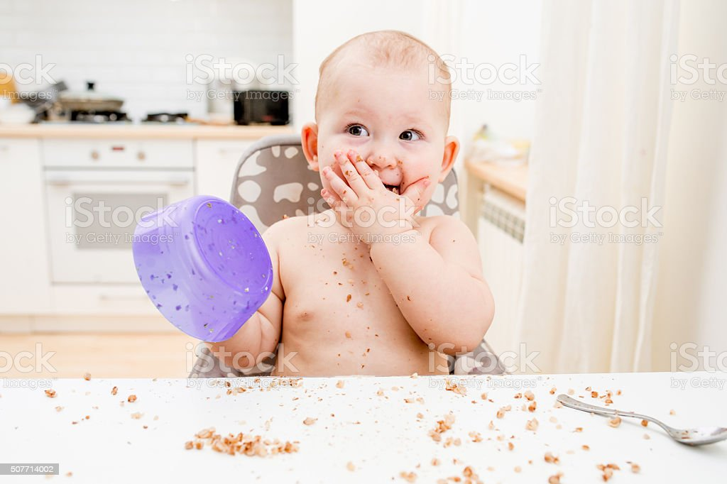 Little baby eating at kitchen. Happy messy eater stock photo