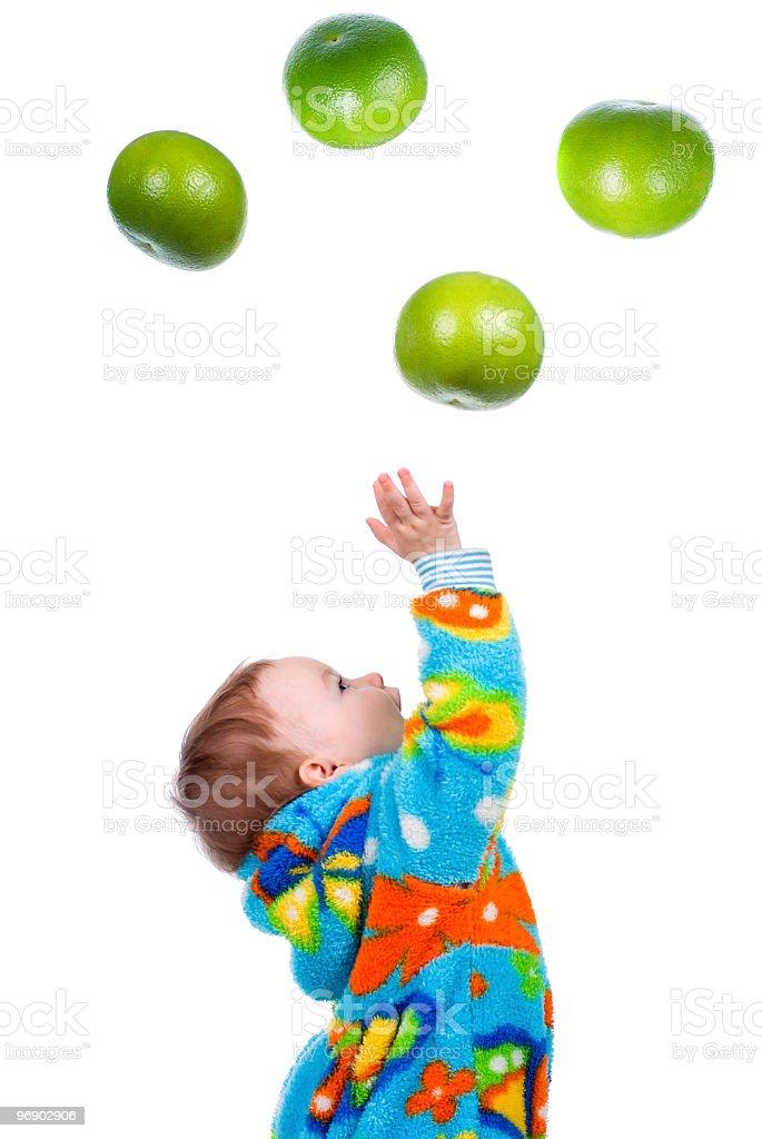 Little baby girl caughts fruits -grapefruit stock photo