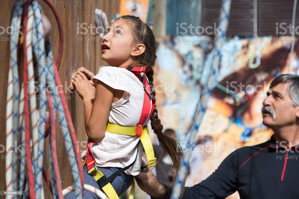 Little baby girl climbs wall grandfather assisting her stock photo