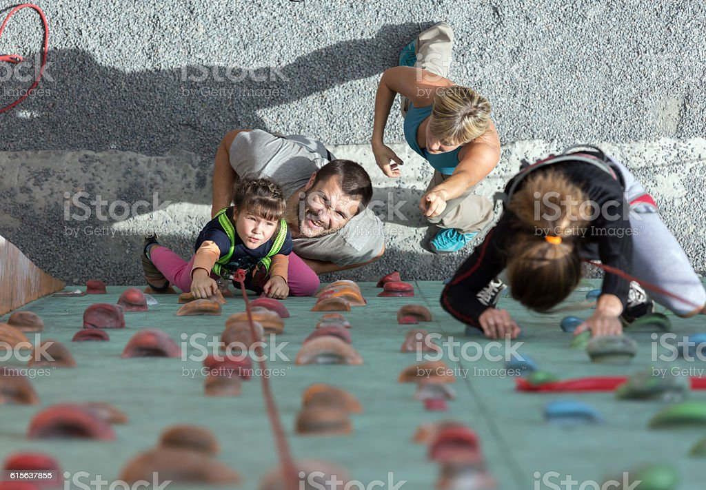 Little baby girl doing first steps on climbing wall stock photo