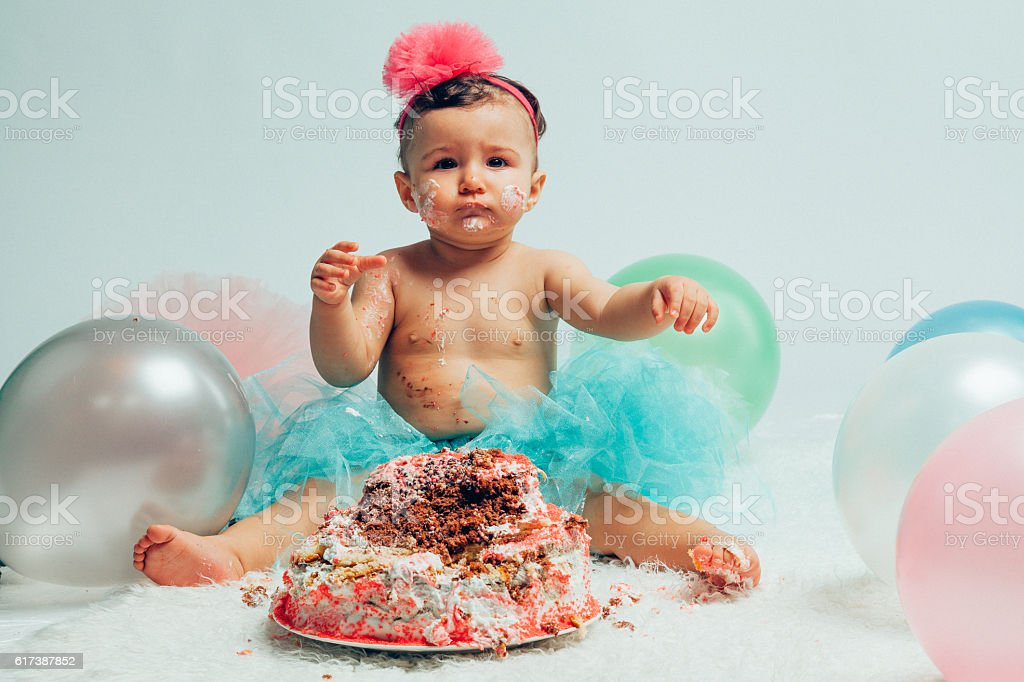Little baby girl eating birthday cake during cake smash party stock photo