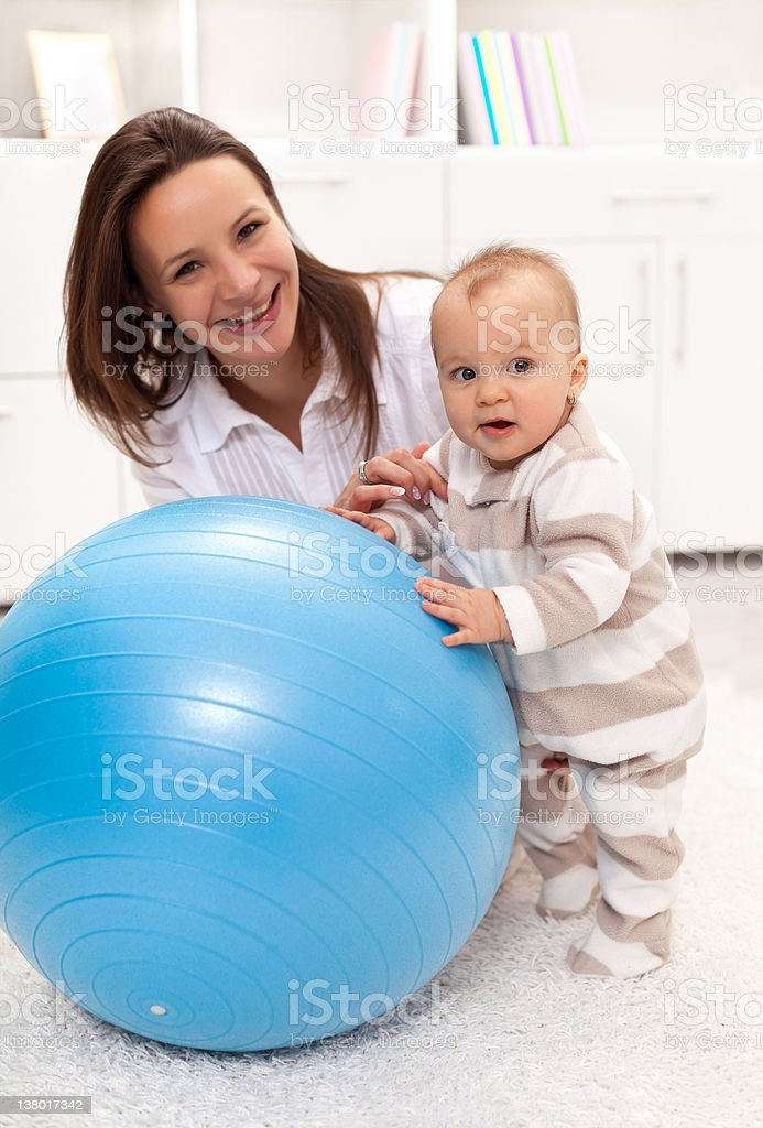 Little baby girl stands by a large exercise ball royalty-free stock photo