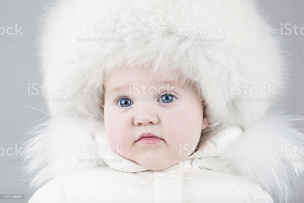Little baby girl wearing huge fur hat and winter suit stock photo