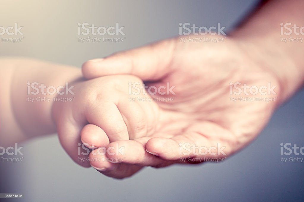 little baby hand holding his mother finger stock photo