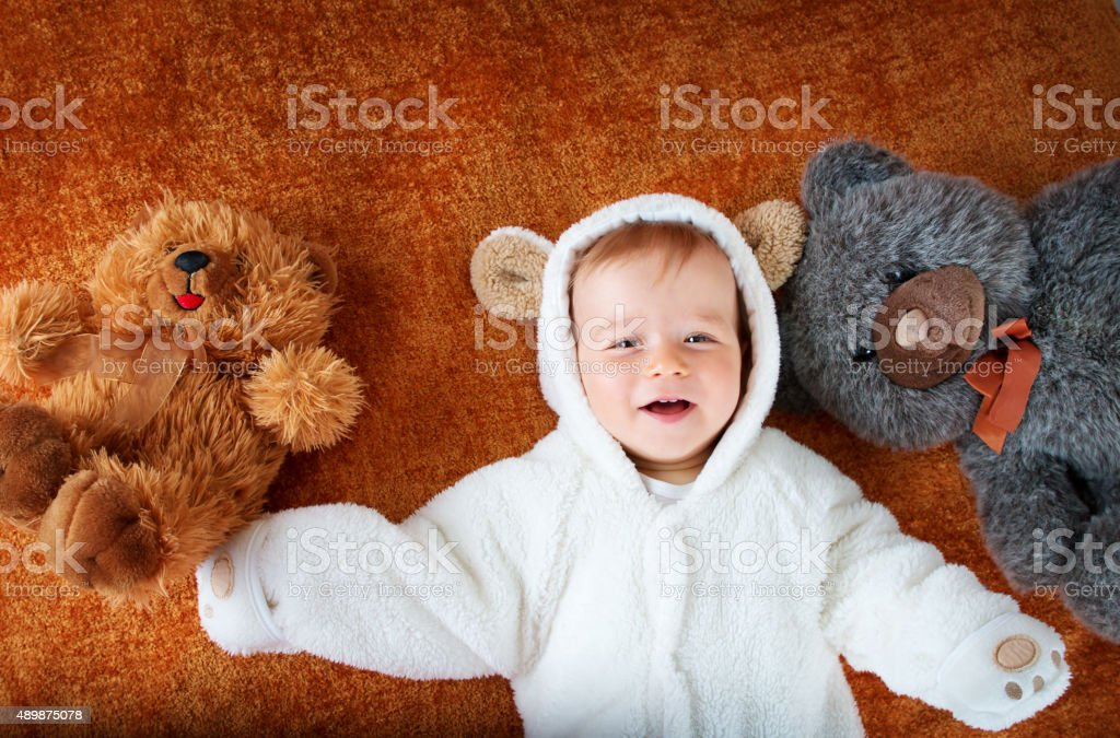 Little baby in bear costume with plush toys stock photo