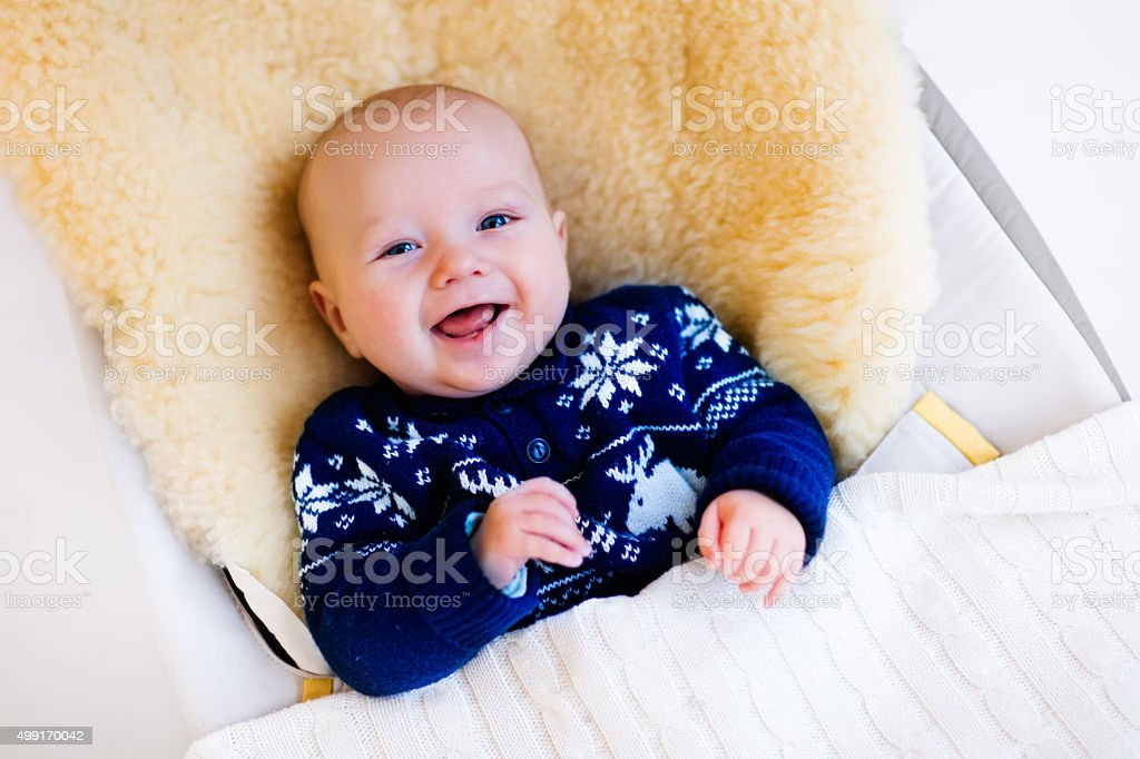 Little baby in nordic sweater on sheepskin muff stock photo