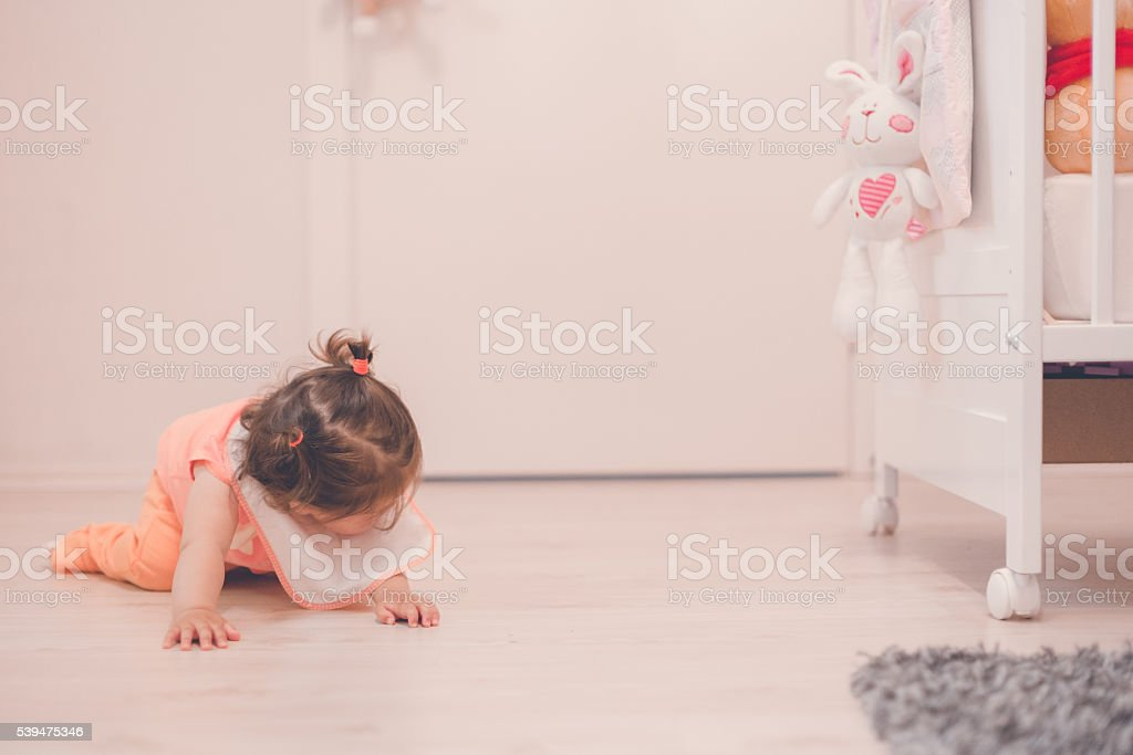little baby looking underneath a crib stock photo