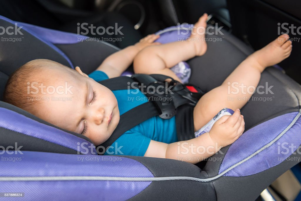 Little baby sitting in a car stock photo
