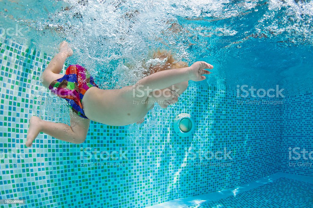 Little baby swimming and diving in pool with fun stock photo