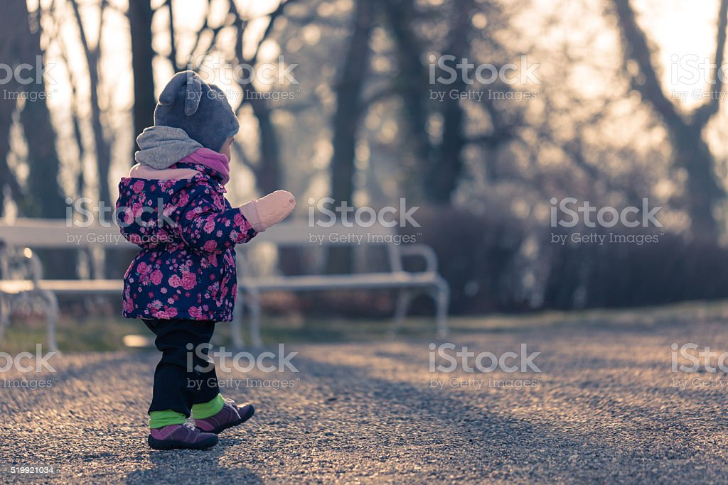 Little baby toddler exploring cold outside world in park stock photo