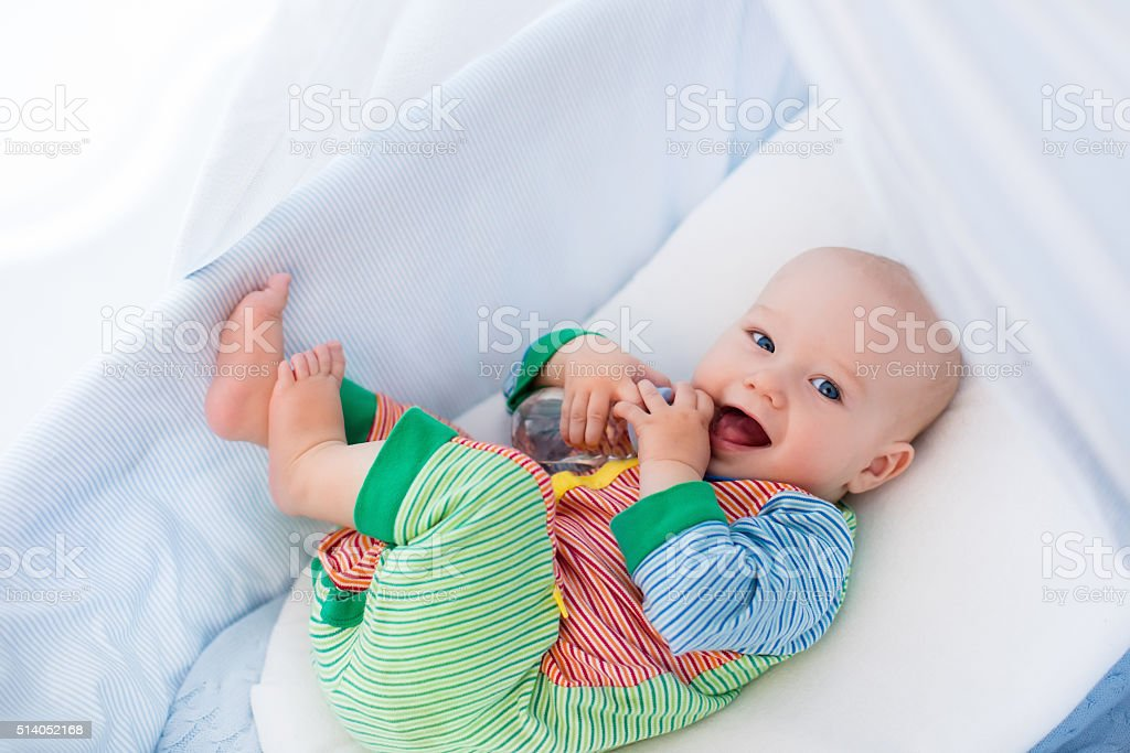 Little baby with bottle in white bed stock photo