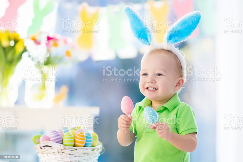 Little baby with bunny ears on Easter egg hunt stock photo
