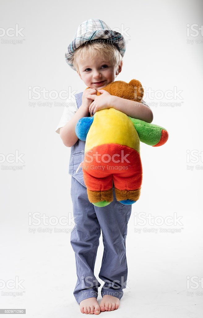 little baby with hat hugging his teddy bear stock photo