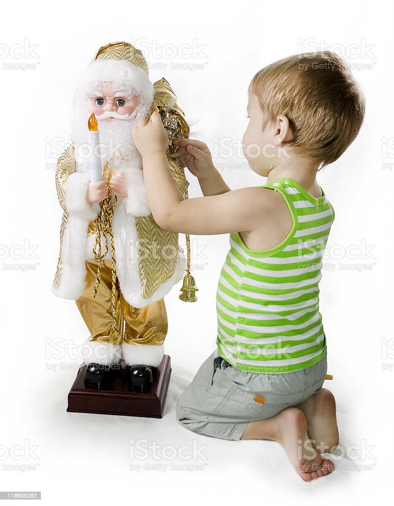 Little barefooted Boy and toy Santa Claus royalty-free stock photo