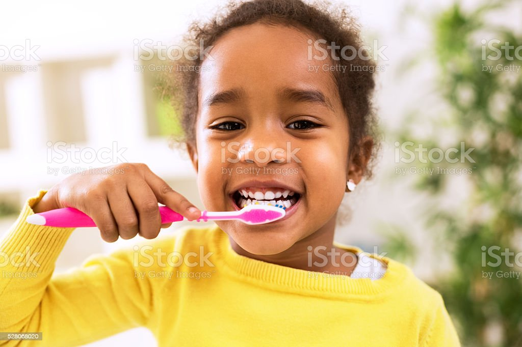 Little beautiful african girl brushing teeth stock photo