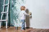 Little beautiful and happy child in jeans paint the wall