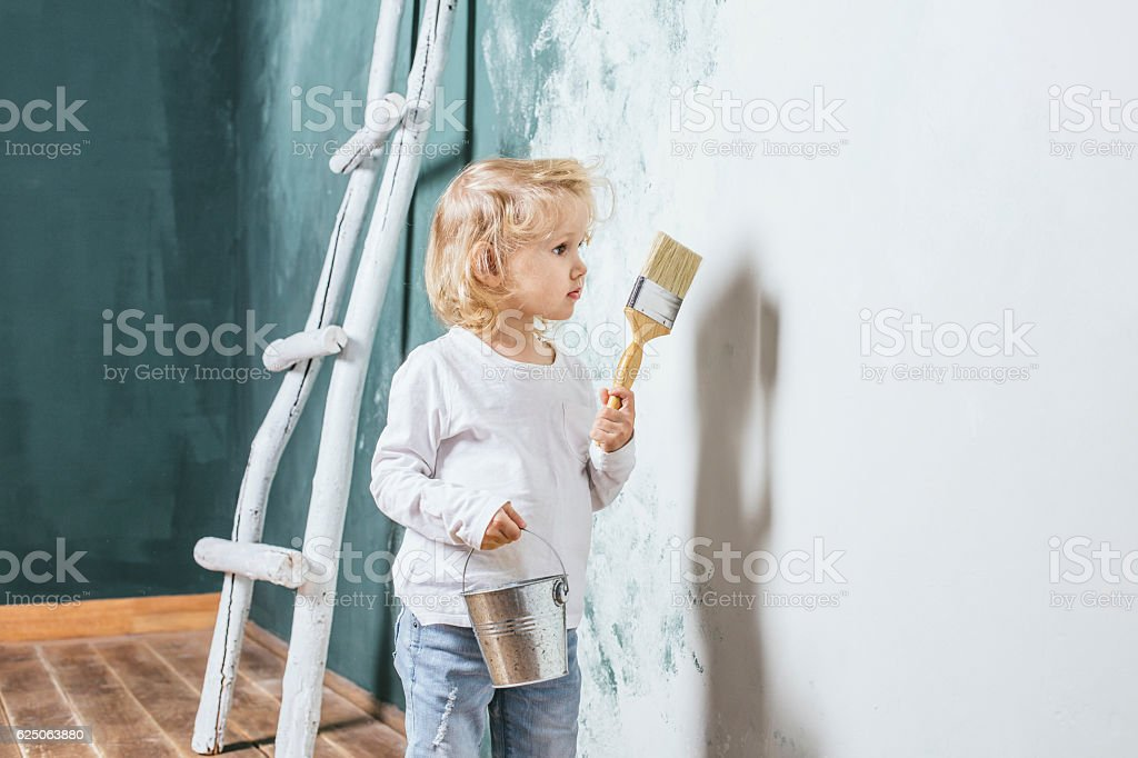 Little beautiful and happy child in jeans paint the wall stock photo