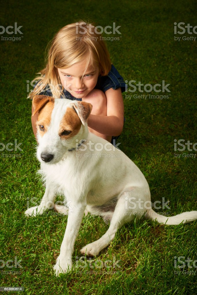 Little beautiful child young girl playing with her parson russell terrier in park. Happy friends leisure outdoors. stock photo