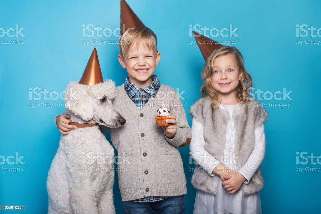 Little beautiful girl and handsome boy with dog celebrate birthday. Friendship. Family. Studio portrait over blue background stock photo