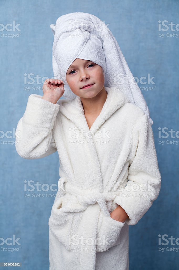 Little beautiful girl in a white bathrobe stock photo