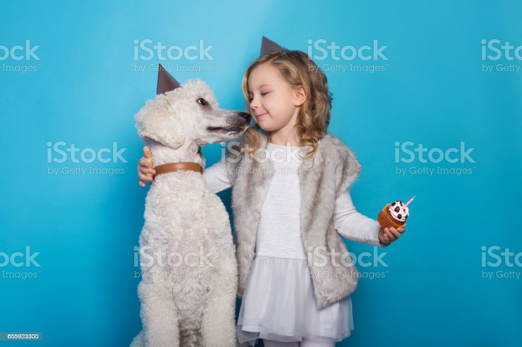 Little beautiful girl with dog celebrate birthday. Friendship. Love. Cake with candle. Studio portrait over blue background stock photo