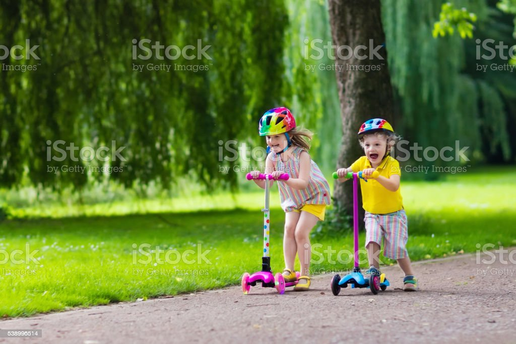 Little beautiful kids riding colorful scooters in summer park stock photo